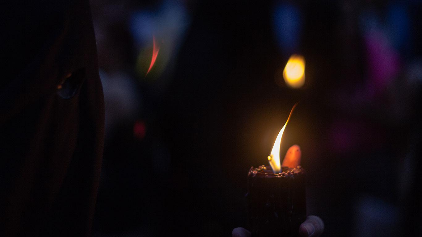 Un nazareno de Santa Cruz observa la llama de su cirio