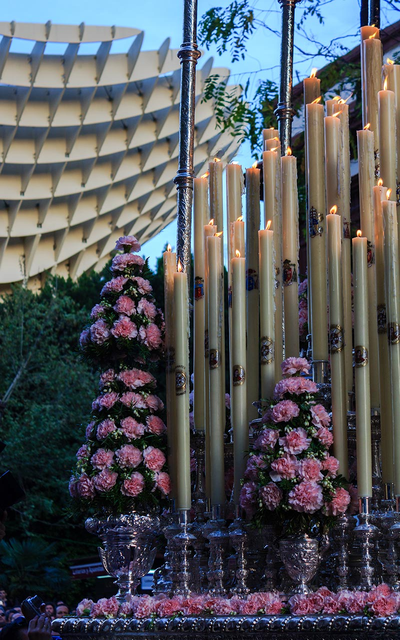 Exorno floral cónico del palio del Valle con la Encarnación de fondo
