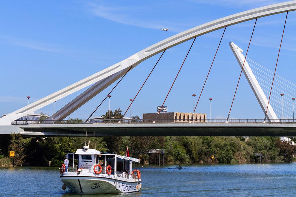Un barco cruza el Puente de la Barqueta en el río Guadalquivir
