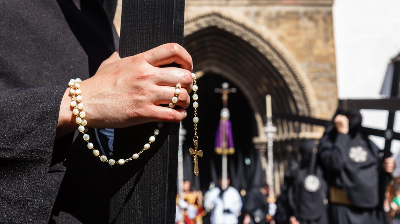 Penitente con rosario saliendo de Omnium Sanctorum