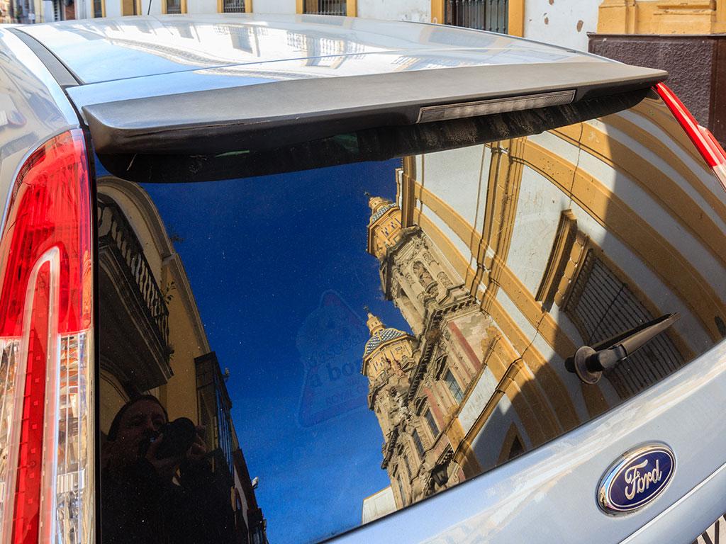 La iglesia de San Luis de los Franceses reflejada en la luneta de un coche
