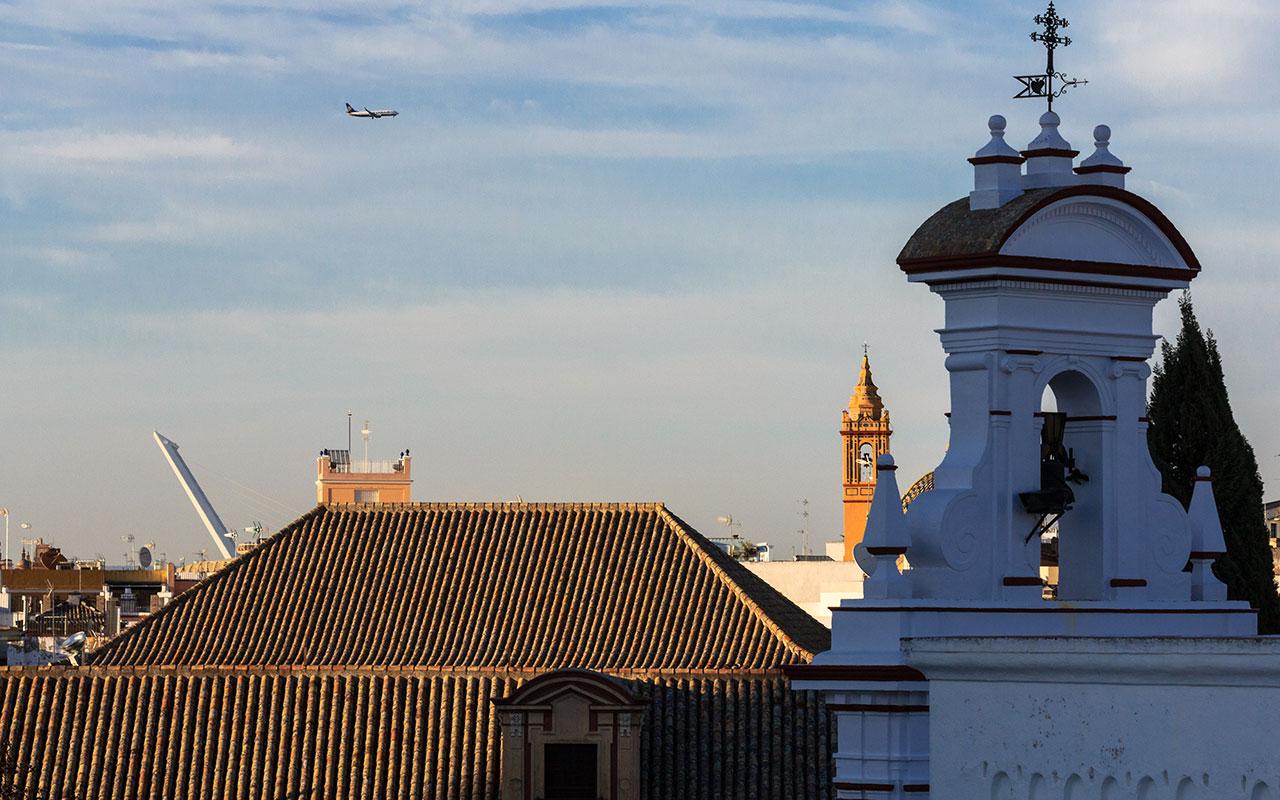 Avión por el cielo de la Plaza Virgen de los Reyes