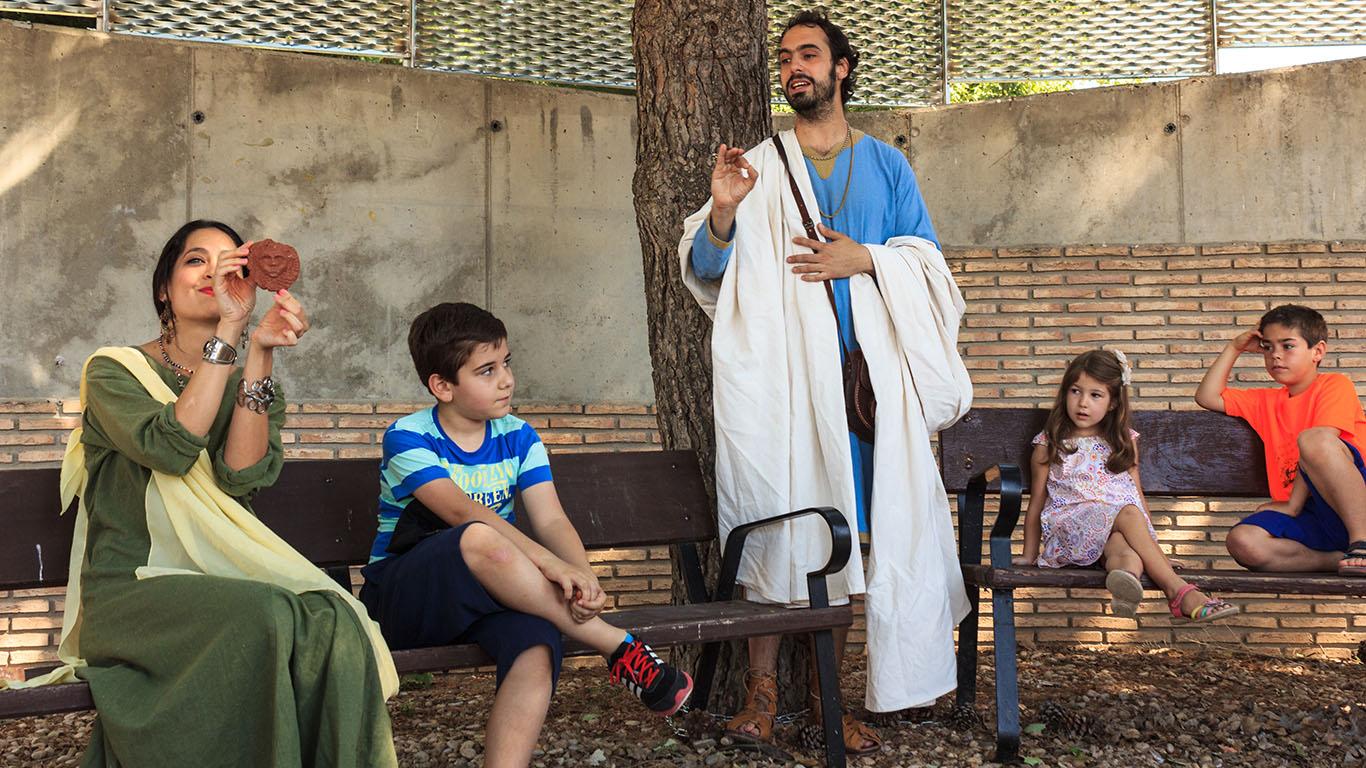 Personajes enseñando a los niños cómo era la vida en la época romana