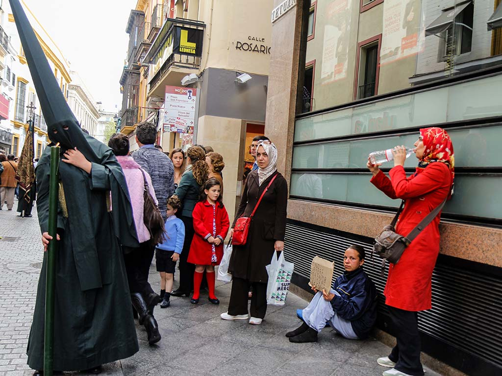 Una mendiga entre unas mujeres árabes al paso de la cofradía del Sol